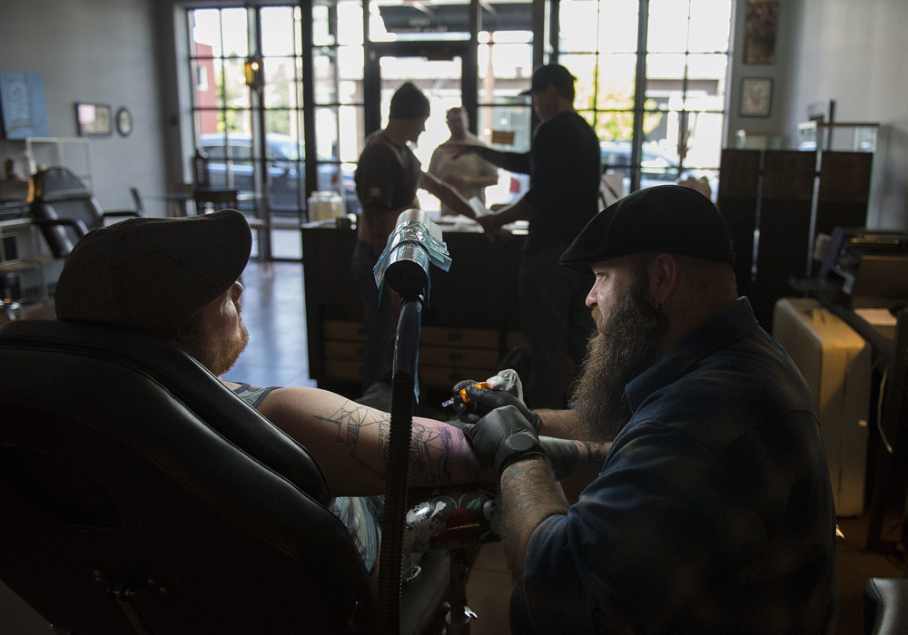 "A lamp illuminates customer Joel Schmid of Camas, left, as he chats with tattoo artist Ryan ""Boomer"" Boomhower while getting a tattoo with a Columbia River Gorge theme at 3rd Heart Tattoo on Tuesday afternoon, Oct. 6, 2015 in Washougal. (Amanda Cowan/The Columbian)"